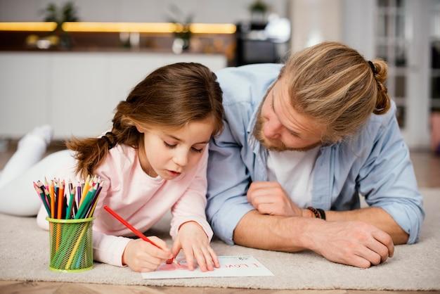 Vista frontal de la niña pasar tiempo con el dibujo del padre