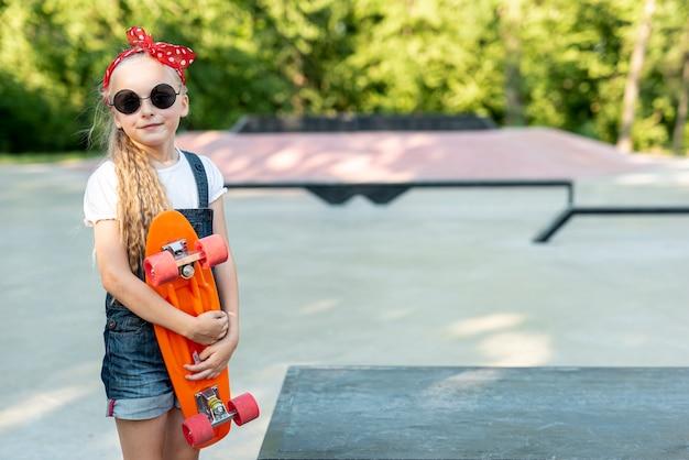 Vista frontal de la niña con patineta naranja