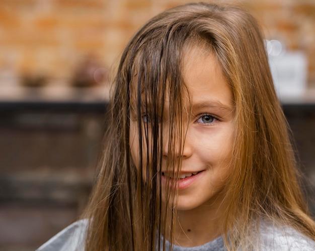Vista frontal de la niña en la peluquería