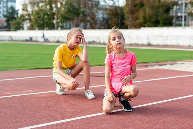 Vista frontal de la niña en la pista de atletismo