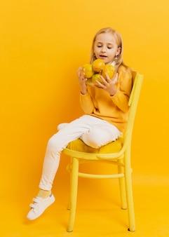 Vista frontal de la niña posando mientras sostiene limones