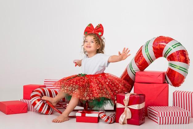 Vista frontal niña rodeada de elementos navideños