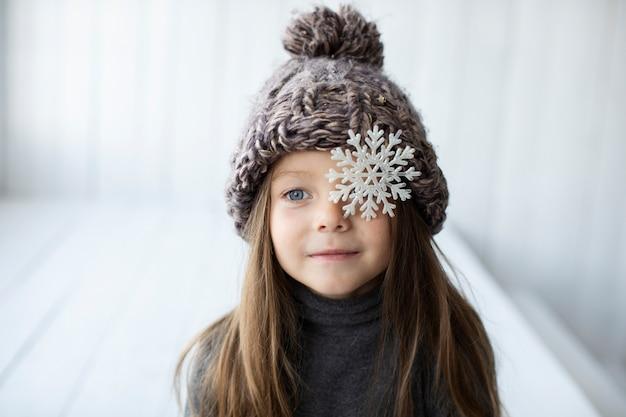 Vista frontal niña rubia con sombrero de invierno