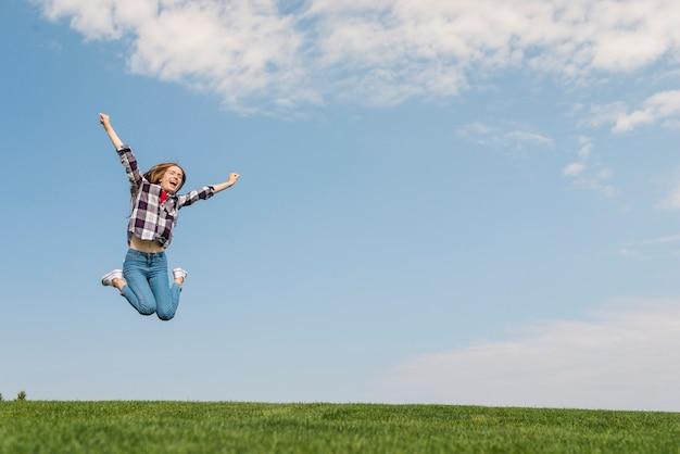 Vista frontal niña saltando tan alto como puede