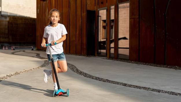 Vista frontal de la niña con scooter azul