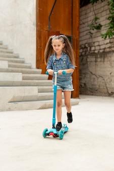 Vista frontal de la niña en scooter azul