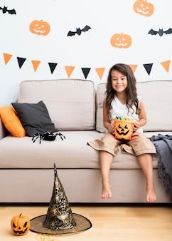 Vista frontal niña sentada en el sofá en halloween