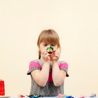 Vista frontal de la niña con síndrome de down jugando