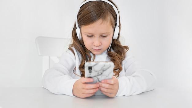 Vista frontal de la niña con smartphone y auriculares en casa