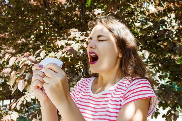 Vista frontal de una niña soltera que estornuda y sopla al aire libre con un fondo verde