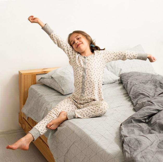 Vista frontal de la niña sonriente en la cama