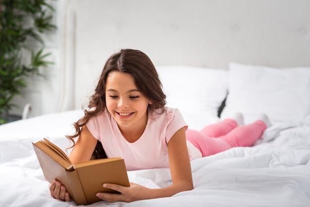 Vista frontal niña sonriente en casa leyendo en la cama