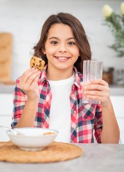 Vista frontal niña sonriente desayunando