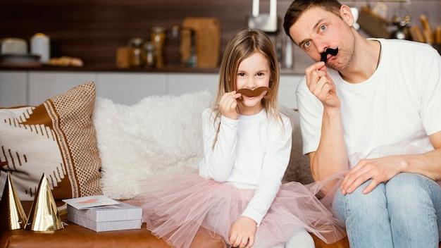 Vista frontal de la niña sonriente en falda tutú y padre con bigotes falsos