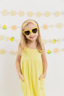 Vista frontal de la niña sonriente con gafas de sol