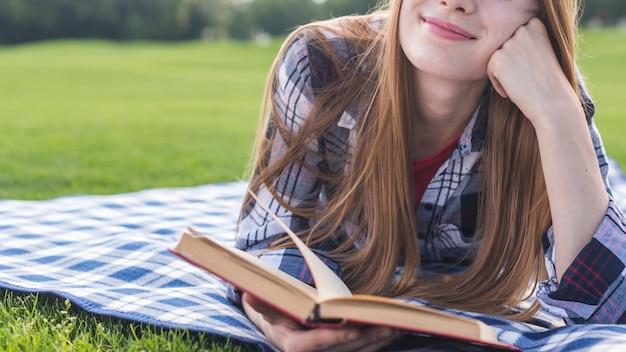 Vista frontal niña sonriente leyendo un libro