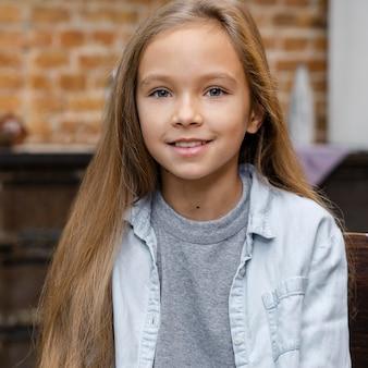 Vista frontal de la niña sonriente con el pelo largo