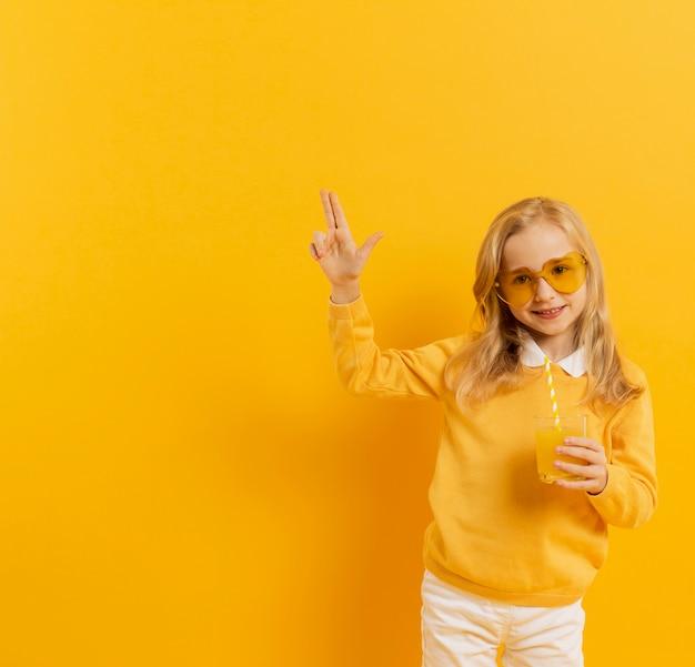 Vista frontal de la niña sonriente posando con gafas de sol y vaso de jugo