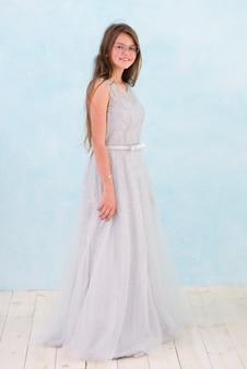 Vista frontal de la niña sonriente con un vestido elegante
