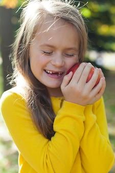 Vista frontal de una niña sosteniendo una granada con los ojos cerrados.