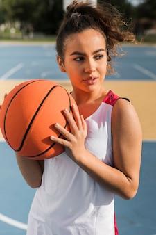 Vista frontal de la niña sosteniendo la pelota de baloncesto