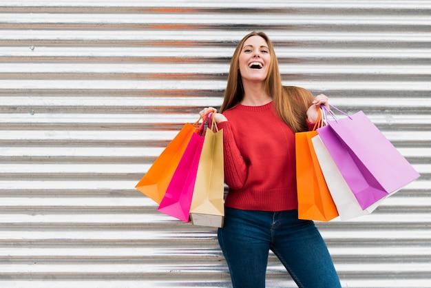 Vista frontal, niña, tenencia, bolsas de compras