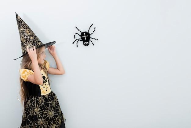 Vista frontal niña en traje de bruja con espacio de copia