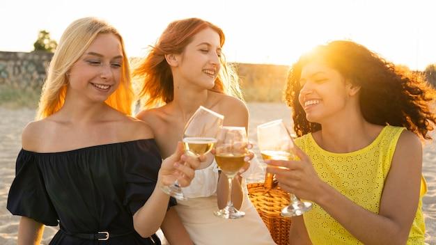 Vista frontal de las niñas bebiendo vino en la playa