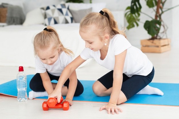 Vista frontal de las niñas en casa en la estera de yoga con pesas