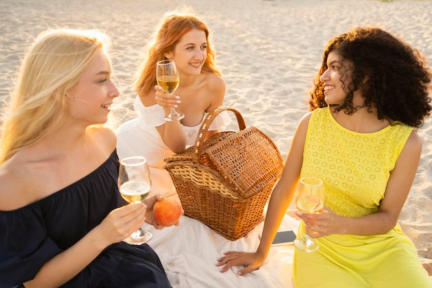Vista frontal de las niñas haciendo un picnic en la playa