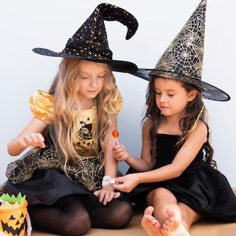 Vista frontal niñas sentadas en el piso en halloween