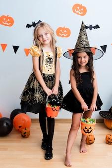 Vista frontal de niñas en traje de bruja para halloween