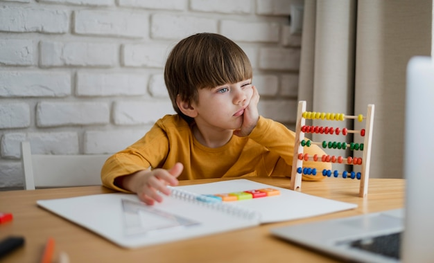 Vista frontal del niño con ábaco aprendiendo de la computadora portátil en casa
