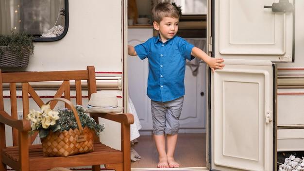 Vista frontal niño abriendo la puerta de una caravana