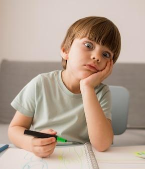 Vista frontal del niño aburrido en casa mientras recibe la tutoría