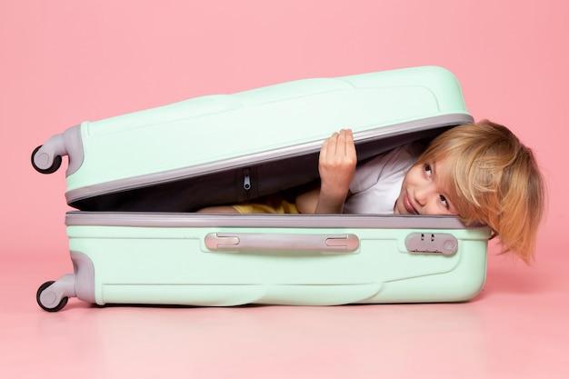 Vista frontal del niño acostado dentro de la bolsa en el piso rosa