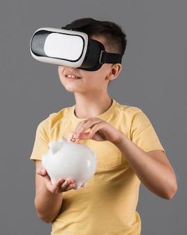 Vista frontal del niño ahorrando dinero mientras usa casco de realidad virtual