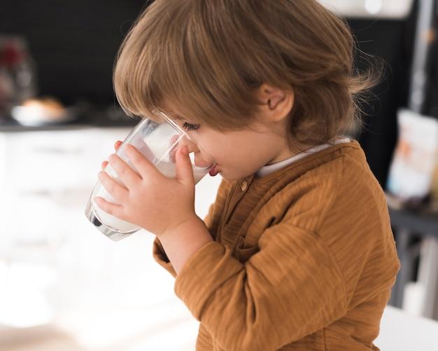 Vista frontal niño bebiendo un vaso de leche