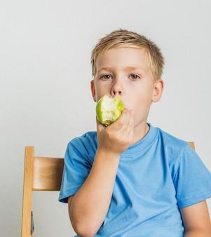 Vista frontal niño con cabello rubio mordiendo una manzana