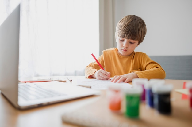Vista frontal del niño en casa dibujando con la ayuda de una computadora portátil