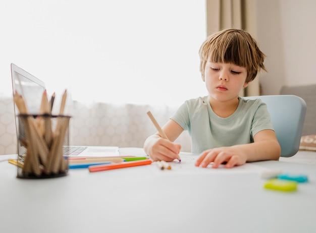 Vista frontal del niño escribiendo y aprendiendo en casa