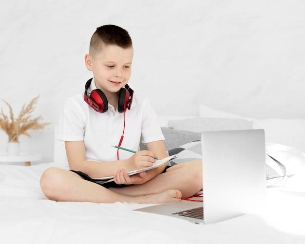 Vista frontal niño feliz aprendiendo en línea