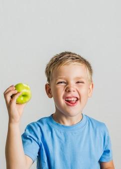 Vista frontal niño feliz con una manzana