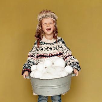 Vista frontal niño feliz con sombrero y bolas de nieve