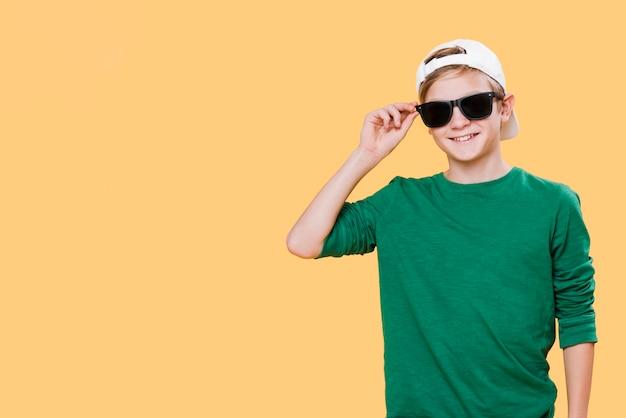 Vista frontal del niño con gafas de sol y espacio de copia