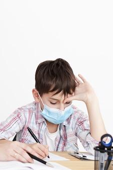 Vista frontal del niño haciendo la tarea mientras usa una máscara médica