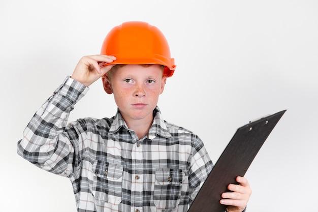 Vista frontal niño haciéndose pasar por trabajador de la construcción
