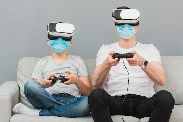 Vista frontal del niño y el hombre jugando con casco de realidad virtual mientras usa máscaras médicas