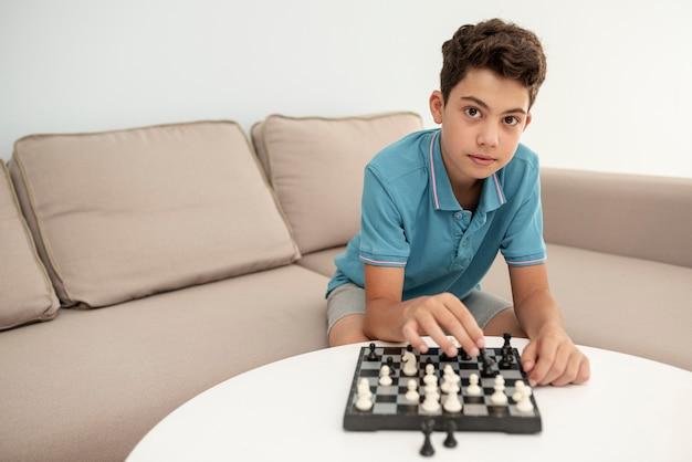 Vista frontal niño jugando al ajedrez