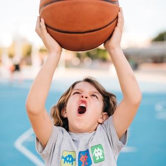 Vista frontal del niño jugando baloncesto